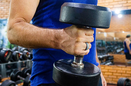 Man holding dumbell wearing Swagmat silicone ring for men